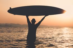 Silhouette of man holding surfboard at sunset over sea. Tourist guy in hat standing in water and holding up surfboard at sunset. Freedom and summer vacation Stock Photo