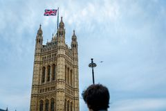 A tourist guy looks at the Victoria Tower at the Palace of Westminster on a sunny day, UK. A tourist guy looks at the Victoria Tower at the Palace of Westminster royalty free stock photography