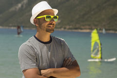 Tourist guy portrait and wind surfers in the background at the beach stock image