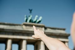 Tourist or guy shows his hand on the Brandenburg Gate in Berlin. In Germany during the sightseeing royalty free stock photos