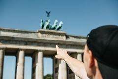 Tourist or guy shows his hand on the Brandenburg Gate in Berlin. In Germany during the sightseeing royalty free stock photo