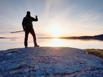 Tourist guy taking pictures of amazing sea landscape on mobile phone digital camera. Stock Image