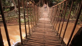 Tourist guy walks on a suspension bridge made of bamboo in the jungle. stock video footage