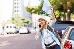Tourist hailing taxi. Female tourist hailing a taxi in the city Royalty Free Stock Image