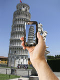 Tourist halten Kameratelefon an lehnendem Turm von Pisa Stockbild