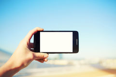 Tourist hand holding cell phone while taking a photograph of landscape in summer travel Royalty Free Stock Images