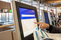 Tourist hand touching display at self-service transfer machine,. Buying airplane or train tickets at automatic device at international airport stock photography