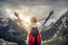 Tourist with hands up stands on the background of a mountain landscape. Tourist with their hands up stands on the background of a mountain landscape Stock Images
