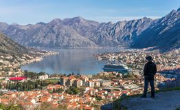Looking at the Kotor bay from above. Tourist with a hat admiring the stunning landscape of the Bay of Kotor in Montenegro as seen from the road to Lovcen royalty free stock photo