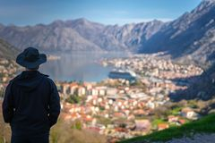 Looking at the Kotor bay from above. Tourist with a hat admiring the stunning landscape of the Bay of Kotor in Montenegro as seen from the road to Lovcen stock photo