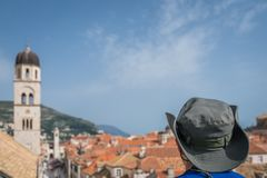 Tourist with a hat in Dubrovnik. Head of a caucasian male tourist wearing a hat and looking at the Old Town in Dubrovnik, Croatia royalty free stock images