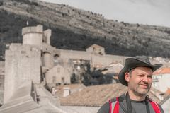Tourist with a hat in Dubrovnik. Head of a caucasian male tourist wearing a hat and walking on the historical Walls of the Old Town in Dubrovnik, Croatia royalty free stock photo