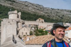 Tourist with a hat in Dubrovnik. Head of a caucasian male tourist wearing a hat and walking on the historical Walls of the Old Town in Dubrovnik, Croatia royalty free stock photography