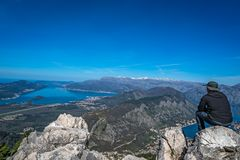 Looking at the Kotor bay from above. Tourist with a hat sitting on a large boulder and admiring the stunning landscape of the Bay of Kotor in Montenegro as seen royalty free stock photos