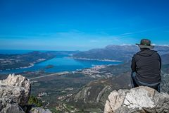 Looking at the Kotor bay from above. Tourist with a hat sitting on a large boulder and admiring the stunning landscape of the Bay of Kotor in Montenegro as seen royalty free stock photography