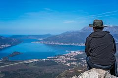 Looking at the Kotor bay from above. Tourist with a hat sitting on a large boulder and admiring the stunning landscape of the Bay of Kotor in Montenegro as seen royalty free stock photo