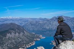 Man admiring Kotor bay from above. Tourist with a hat sitting on a large boulder and admiring the stunning landscape of the Bay of Kotor in Montenegro as seen stock photos