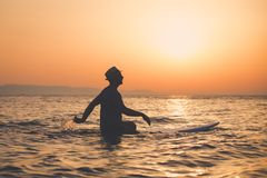 Silhouette of man sitting on surfboard at sunset over sea. Tourist with hat sitting on surfboard in ocean at sunset Royalty Free Stock Image