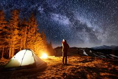 Tourist have a rest in his camp near the forest at night, pointing at beautiful night sky full of stars and milky way. Male tourist have a rest in his camp near Royalty Free Stock Photo