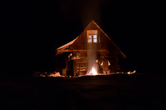 Tourist heated by fire at winter near a wooden cabin Stock Photography