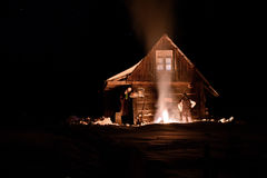 Tourist heated by fire at winter near a wooden hut Royalty Free Stock Photo