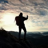 Tourist with heavy backpack takes photos with smart phone. Man on the rocky peak. Dreamy fogy valley below Stock Photography