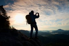 Tourist with heavy backpack takes photos with smart phone. Man on the rocky peak. Dreamy fogy valley below Stock Image