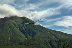 Tourist helicopter against the backdrop of volcano Priemysh. South Kamchatka Nature Park. Royalty Free Stock Photo