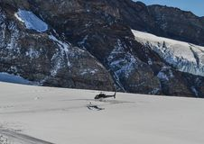 Tourist helicopter landing on the glacier stock photo