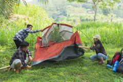 Tourist help each other prepare tent. Couple tourist help each other prepare tent at natural lake in background Stock Photos