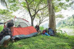 Tourist help each other prepare tent. Couple tourist help each other prepare tent at natural lake in background Royalty Free Stock Photography