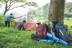 Tourist help each other prepare tent. Couple tourist help each other prepare tent at natural lake in background Royalty Free Stock Photos