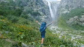 Tourist hiker with a backpack raises his hands up and turns around himself against the backdrop of a huge waterfall in. The mountains. Concept of victory stock photos