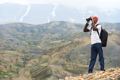 Tourist hiker with binoculars in mountains Royalty Free Stock Image