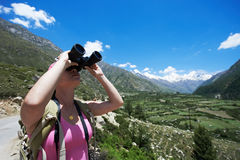 Tourist hiker with binoculars in mountains. One tourist traveller hiker with binoculars in Himalayas mountains Royalty Free Stock Photography