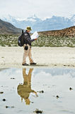 Tourist hiker with compass and map in mountains Stock Images