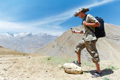 Tourist hiker with compass in mountains Stock Images