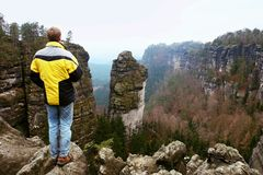 Tourist hiker man on the rock peak  in rocky mountains Royalty Free Stock Photo