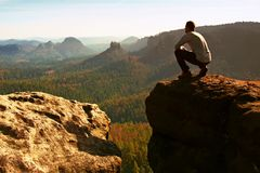 Tourist hiker man on the rock peak  in rocky mountains Stock Images