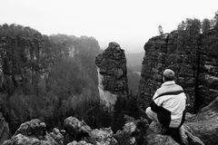 Tourist hiker man on the rock peak  in rocky mountains Stock Photos