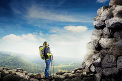 Tourist with hiker poles looking up. Amazed tourist with hiker poles looking up at rock over beautiful landscape Royalty Free Stock Photography