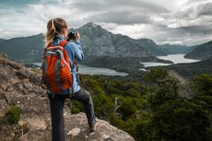 Lady hiker. Tourist hiker with red backpack takes pictures of the valley with mountains and lakes. Patagonia, Argentina stock photo