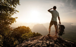 Tourist. Hiker on top of the mountain enjoying sunrise over the tropical valley Stock Photo