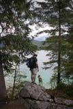 Tourist hiking on alpine lake with dog stock photography