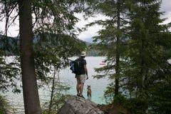Tourist hiking on alpine lake with dog royalty free stock image