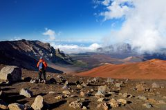Tourist hiking in Haleakala volcano crater on the Sliding Sands trail. Beautiful view of the crater floor and the cinder cones bel. Ow. Maui, Hawaii, USA Stock Photo