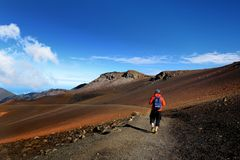 Tourist hiking in Haleakala volcano crater on the Sliding Sands trail. Beautiful view of the crater floor and the cinder cones bel. Ow. Maui, Hawaii, USA Royalty Free Stock Image