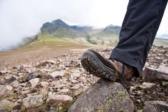 Tourist in hiking shoes atop the mountain Royalty Free Stock Photography