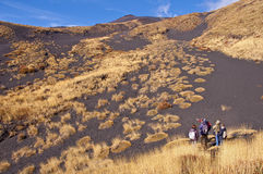 Tourist hiking on a trail on the Etna volcano Royalty Free Stock Images