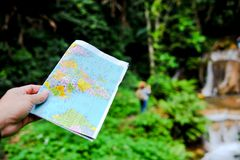 A tourist and his map on a trip to the forest in Thailand. Rich stock images